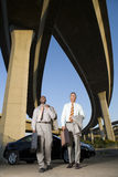 Two businessmen by car with briefcases beneath overpasses, low angle view Stock Image