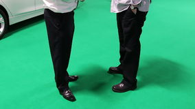 Two businessmen and car on green background. Two businessmen talking at a car showroom standing on the bright green floor with a brand new white car behind stock video