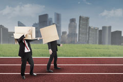 Two businessmen with cardboard on the track Stock Photo