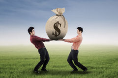 Two businessmen carrying a money bag Stock Images
