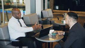 Two multiracial businessmen in formal clothes smiling, gesturing and discussing their startup in spacious cafe during. Two businessmen of Caucasian and African stock footage