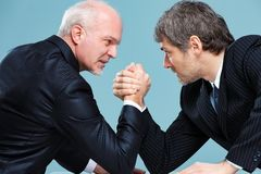Two businessmen challenging each other. For a leadership position, trying to dominate by arm wrestling, and staring into each others eyes stock photos