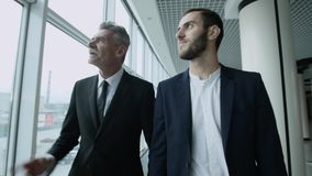 Two businessmen chat together as they walk along through a busy modern office building.  stock footage