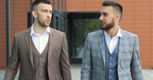 Two businessmen chat together as they walk along through a busy modern office building. Two young friendly businessmen communicating with carefree morning stock video footage