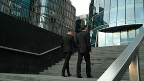 Two businessmen climb the stairs. Two young friendly businessmen communicating with carefree morning conversation. They climbing the stairs. Glass business stock video footage
