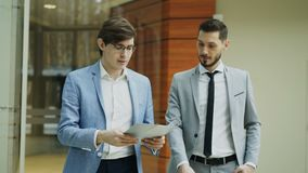 Two businessmen colleagues walking and discussing documents in modern office hall. Indoors stock footage