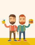 Two businessmen comparing apple to hamburger Stock Image