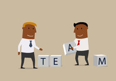 Two businessmen composing word Team from cubes. Business partnership, team building work or cooperation business concept. Creative businessmen with alphabet Royalty Free Stock Photography