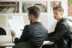 Two businessmen coworkers analyzing financial stats report. stock image