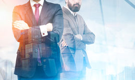 Two businessmen with crossed arms in office, skyscrapers Royalty Free Stock Photography