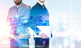 Two businessmen with crossed arms in office, skyscrapers and nig Royalty Free Stock Photo