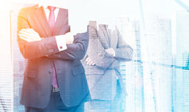 Two businessmen with crossed arms in office, skyscrapers and sun Stock Images