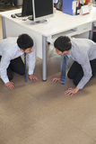 Two businessmen crouching on the floor Royalty Free Stock Image