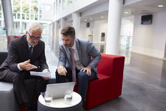 Two Businessmen Discuss Document In Lobby Of Modern Office Stock Photography