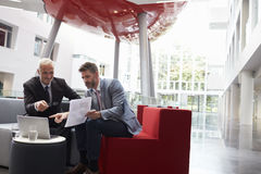 Two Businessmen Discuss Document In Lobby Of Modern Office Stock Photos
