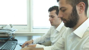 Two businessmen discuss in the office a development plan stock video