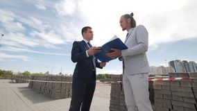 Two businessmen discuss plans for future construction stock footage