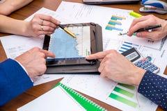 Two businessmen discuss schedule of sales through stock photos