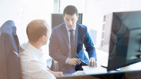 Two businessmen discussing a bisiness problem at meeting in trading office. Royalty Free Stock Image