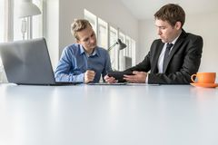 Two businessmen discussing data on a tablet Stock Image