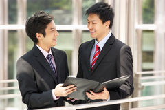 Two Businessmen Discussing Document Outside Office Stock Photo