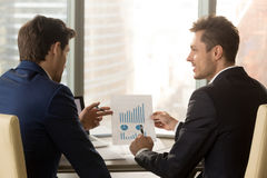 Two businessmen discussing financial report with charts graphs,. Rear view of two businessmen discussing financial report sitting at office desk, holding Royalty Free Stock Photo