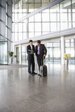 Two businessmen discussing papers in the foyer of an office building Royalty Free Stock Photography