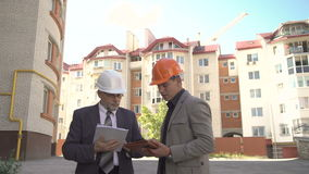 Two businessmen discussing scheme of building near builds. 4K stock video footage