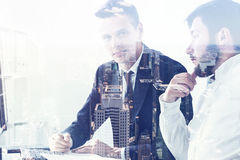 Two businessmen discussing stuff in office, city Stock Images