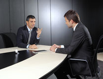 Two businessmen. Discussing tasks sitting at office table royalty free stock image