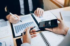 Two businessmen discussion analysis sharing calculations about the company budget and financial planning together on desk at the royalty free stock photos