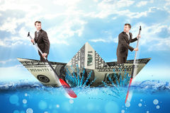Two businessmen in dollar boat Royalty Free Stock Image