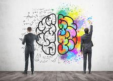 Two businessmen drawing a brain sketch, concrete. Rear view of two businessmen drawing a colorful large brain sketch on a concrete wall. Concept of creativity Stock Images