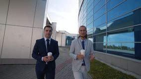 Two businessmen drinking coffee and taking a walk. Two people discuss the interesting details of the Treaty, the movement towards the frame, the man looking at stock video