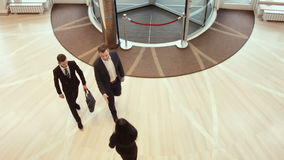 Two businessmen enter a hotel or business center stock footage