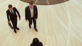 Two businessmen enter a hotel or business center stock video footage
