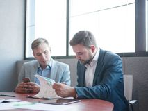 Two businessmen look at papers work in a team stock photos