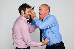Two businessmen fighting. Photo of two businessmen fighting against a plain background, part of a series see my portfolio for them shaking hands and hugging Royalty Free Stock Images