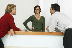 Two businessmen flirting with receptionist at reception desk, smiling Stock Image