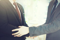 Two businessmen giving warm welcome, trust, teamwork, agreement to each other. Concept royalty free stock image