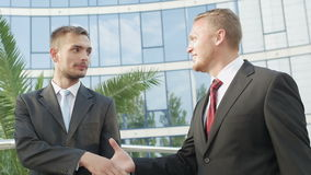 Two businessmen going along office building. Two attractive businessmen going along office building. They kindly communicate and shake hands. In slow motion stock video footage