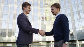 Two businessmen greeting each other by handshake in urban environment. Businessmen greeting by handshake in urban environment stock video