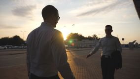 Two businessmen greeting each other outdoor with sun flare at background. Business handshake outdoor. Shaking of male. Arms outside. Colleagues meet and shake stock video