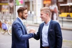 Two businessmen greeting each other in the street. Two handsome businessmen greeting each other in the street stock photography