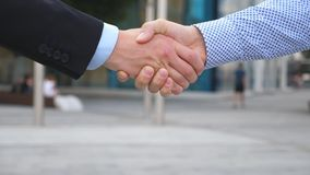 Two businessmen greeting each other in urban environment. Business handshake outdoor. Shaking of male arms outside. Colleagues meet and shake hands in the city stock video