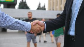 Two businessmen greeting each other in urban environment. Business handshake outdoor. Shaking of male arms outside. Colleagues meet and shake hands in the city stock video footage
