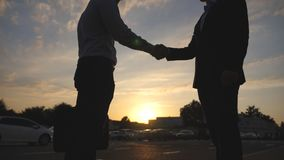 Two businessmen greeting each other in urban environment at sunset. Business handshake outdoor. Shaking of male arms