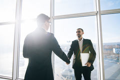 Two businessmen greeting in sunny office room. Against windows stock images