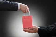 Two businessmen hands with small bag Royalty Free Stock Photography