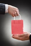 Two businessmen hands with small bag Stock Photo